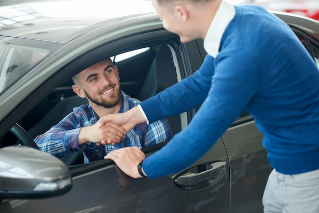 Autoverkäufer und kundenhandschlag im autohaus.