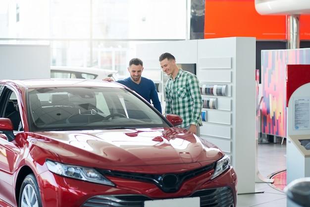 Autoverkäufer zeigt kundenauto im autohaus.