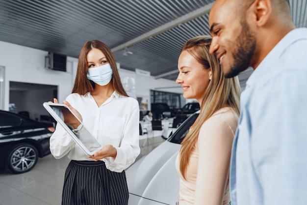 Autoverkäuferin, die medizinische maske trägt, zeigt käuferpaar etwas auf digitalem tablett