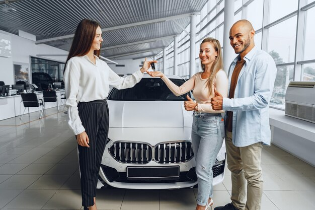 Autoverkäuferin in einem autohaus im gespräch mit kundenkäufern