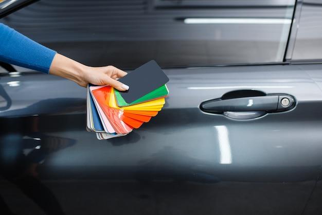 Autoverpackung, männliche hand mit schützender vinylfolie oder filmfarbpalette. arbeiter macht automatische detaillierung. autolackschutzbeschichtung, professionelles tuning