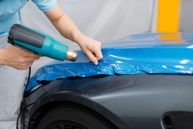 Autoverpackung, mechaniker mit trockner installiert vinyl-folie oder folie auf der fahrzeughaube. arbeiter macht automatische detaillierung. autolackschutzbeschichtung, professionelles tuning