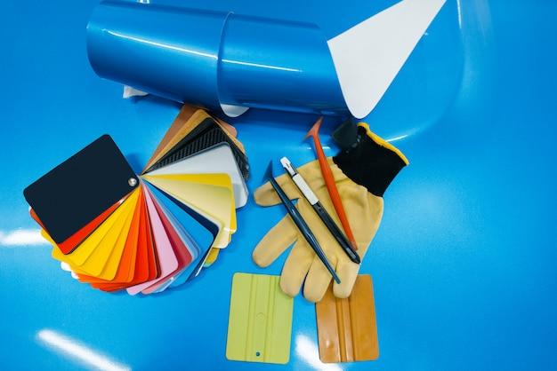 Autoverpackung, schützende vinylfolie oder filmfarbpalette und montagewerkzeuge auf der fahrzeugnahaufnahme, niemand. auto detaillierung. autolackschutz, professionelles tuning