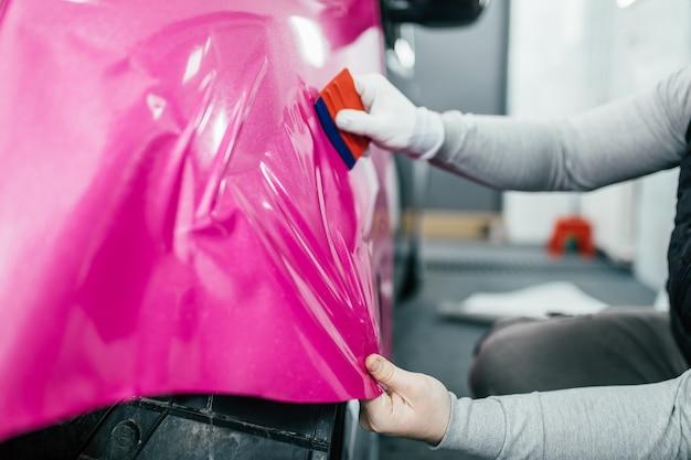 Autoverpackungsspezialist, der vinylfolie oder film auf das auto legt selektiver fokus.