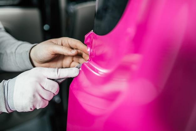 Autoverpackungsspezialist, der vinylfolie oder -folie auf das auto legt. selektiver fokus.