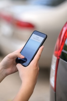 Autoversicherungskonzept, mannhand, die autoversicherungsanwendung am handy hält.