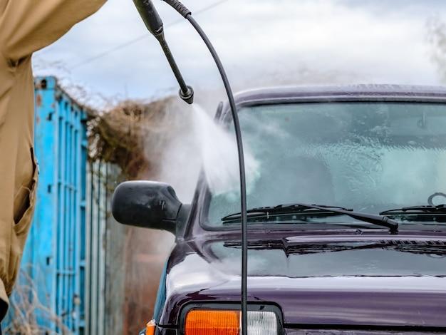 Autowäsche am nachmittag im freien mit einem hochdruckgerät. ein kräftiger wasserstrahl spritzt den schmutz von der lila karosserie des autos, von glas, rädern und reifen weg.