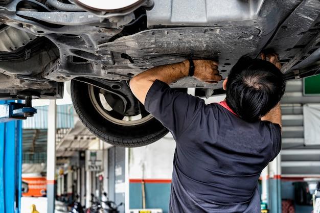 Autowartungskonzept automechaniker, der frisches öl in motor an der wartungstankstelle ersetzt und gießt autoreparaturtechniker gießen neues motoröl, um das alte zu ersetzen