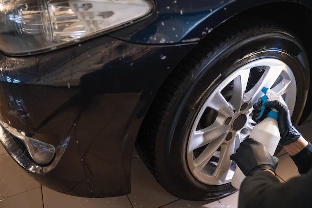 Autowascharbeiter sprüht felgenreiniger.