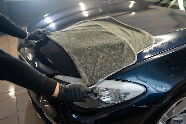 Autowascharbeiter wischt das auto nach dem waschen ab