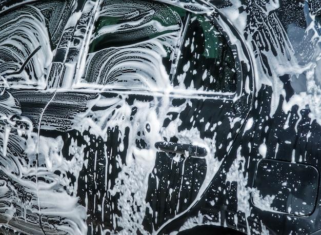 Autowaschblasen mit seife. nahaufnahme des autowaschprozesses.