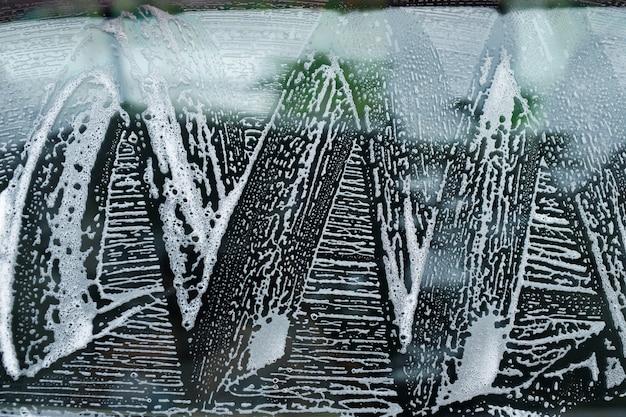 Autowaschschaum und seife im freien auf schwarzem hintergrund. abstraktes muster, banner-hintergrund-konzept. autowasch- und reinigungshintergrund mit textfreiraum.
