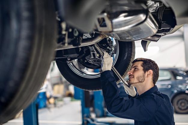 Autowerkstatt. mechaniker, der autoaufhebung überprüft