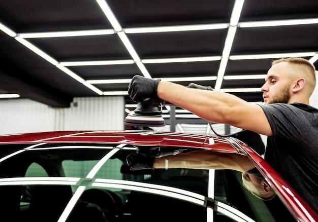 Autowerkstatt poliert autodetails mit einem orbitalpolierer.