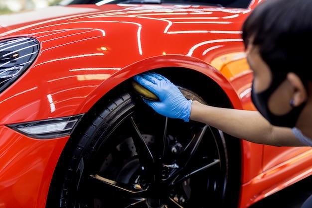 Autowerkstatt poliert autoräder mit mikrofasertuch