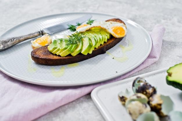 Avacadosandwich mit ei auf toast des schwarzbrots.