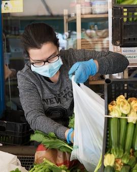 Avetrana, italien, - marth, 13, 2020. ein italienischer gemüsehändler, der einem kunden dient, der während der coronavirus-epidemie eine medizinische maske und handschuhe trägt, die die gesundheitsstandards einhalten.