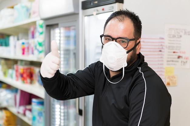 Avetrana, italien, - marth 16, 2020. verkäufer mit medizinischer maske und handschuhen zeigt, dass alles in ordnung sein wird