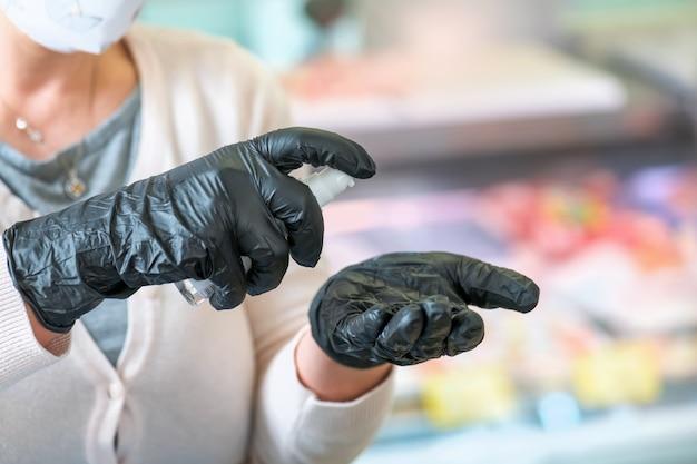 Avetrana, italien, - marth, 21, 2020. schließen sie die hand mit handschuhen und gel-desinfektionsmittel, verkäuferin bei der reinigung ihrer hände mit alkohol-desinfektionsmittel. einkaufen während der pandämie von covid-19