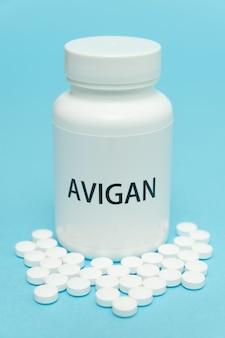 Avigan in weißer flaschenverpackung mit verstreuten pillen zur behandlung von covid19