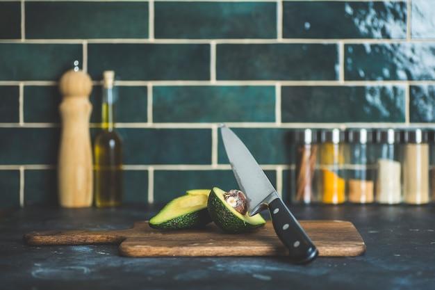Avocado auf dem küchentisch. kochen und avocado-smoothies in der wohnküche. konzept für vitamine und gesunde ernährung