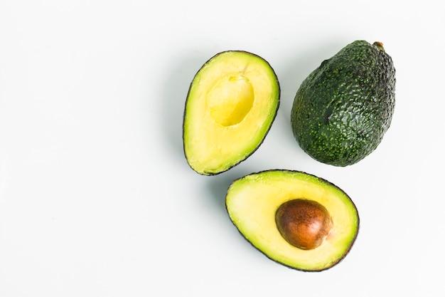 Avocado auf einem dunklen holz hintergrund Kostenlose Fotos