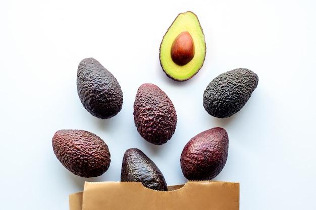 Avocado auf einem weißen hintergrund. früchte liegen verstreut auf dem tisch. zutat für die richtige ernährung