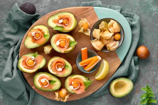 Avocado-boote mit geräuchertem lachs, zitrone, physalis und minzblatt, draufsicht