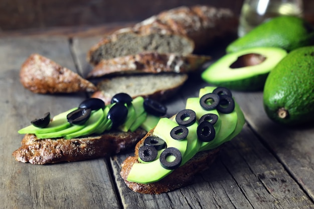 Avocado-brot-oliven auf holzuntergrund