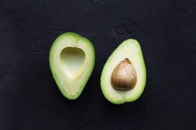 Avocado-frucht auf einem schwarzen tisch