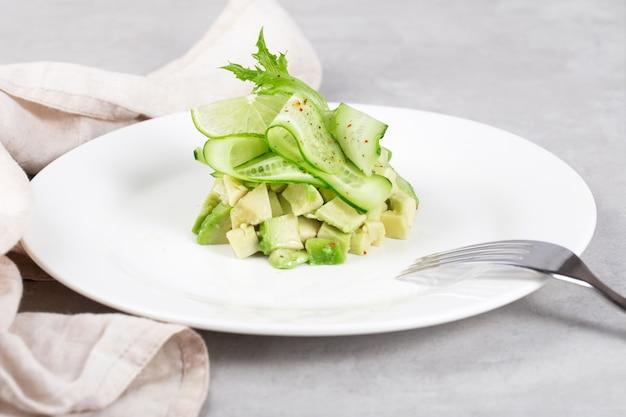 Avocado-gurken-tartar auf einem weißen flachen teller
