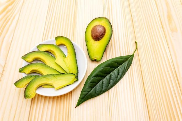 Avocado, halbiert, mit knochen, avocadoscheiben und avocadoblatt