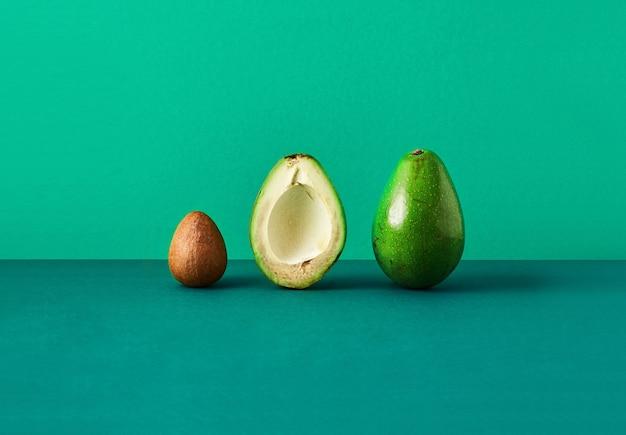 Avocado in zwei hälften geschnitten, knochen von avocado isoliert farbigen hintergrund