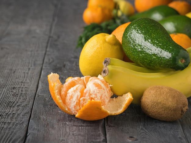 Avocado, mandarinen, orangen, kiwi und bananen auf rustikaler tabelle der weinlese. vegetarisches essen.