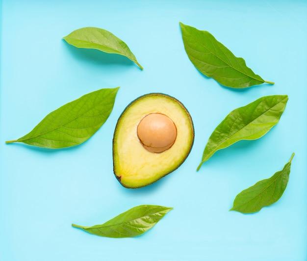 Avocado mit blättern auf blauem hintergrund