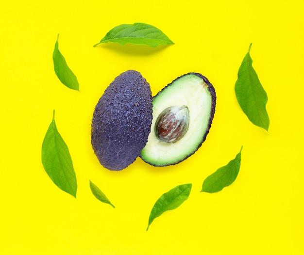 Avocado mit blättern auf gelbem hintergrund