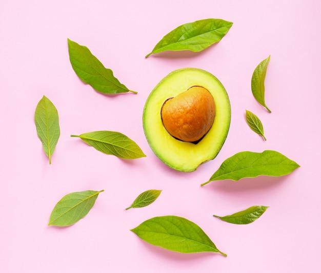 Avocado mit blättern auf rosa hintergrund
