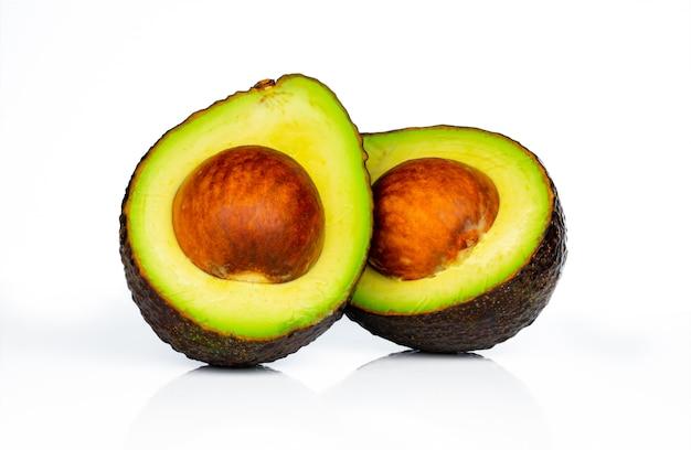 Avocado mit dem samen lokalisiert auf weißem hintergrund. quelle von omega 3 aus natürlichen lebensmitteln. gesundes essen für baby. halbe stücke avocados vereinbarten mit schönem muster. bio-lebensmittel für vegetarier.
