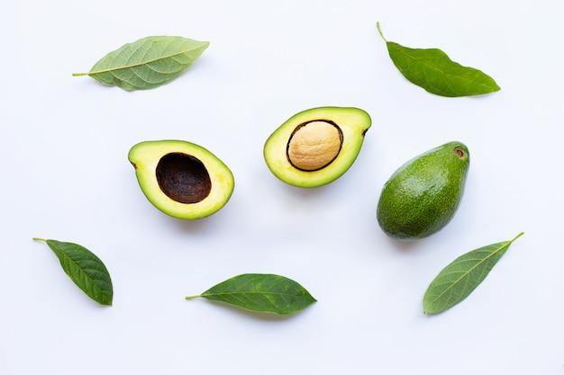 Avocado mit grünen blättern auf einem weiß