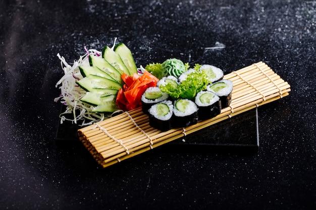Avocado-nori-röllchen mit ingwer-wasabi und gurkenscheiben auf einer sushimatte.
