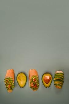 Avocado-sandwich und halbe avocado auf grünem hintergrund. platz kopieren.