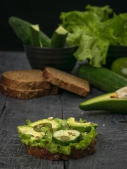 Avocado-scheiben mit gurkenscheiben auf brot auf einem holztisch