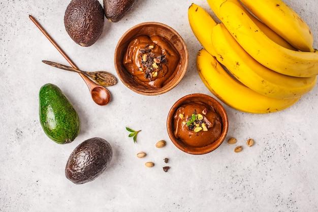 Avocado-schokoladenmousse mit pistazien in einer holzschale auf einem weißen hintergrund