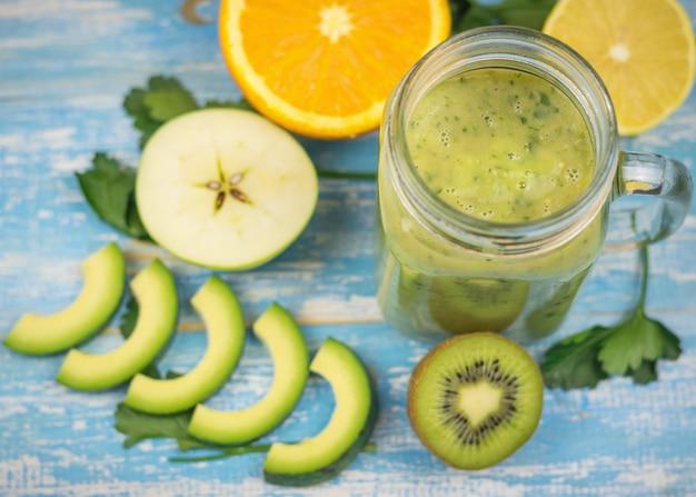 Avocado-smoothie mit geschnittenen früchten aus banane, kiwi, avocado und kräutern