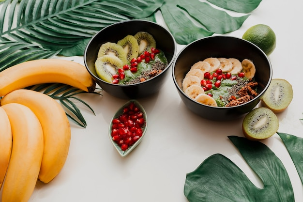 Avocado-smoothie-schüssel mit chia, müsli, kiwi und spinat. oben, draufsicht, flach liegen. gesundes frühstück. tropische blätter.