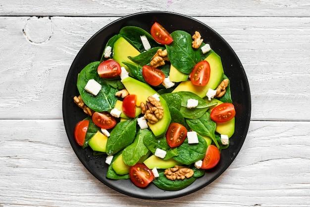 Avocado-spinat-salat mit tomaten kirsche, feta-käse und walnüssen in einem teller auf rustikalem holztisch. draufsicht