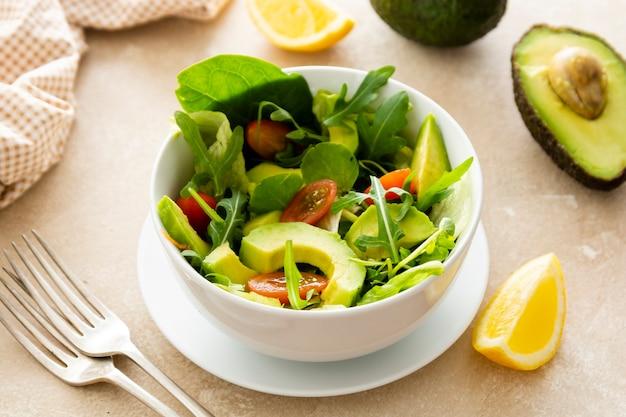 Avocado-spinat-salat mit zitronensaft in einer schüssel mit zwei gabeln auf hellem hintergrund