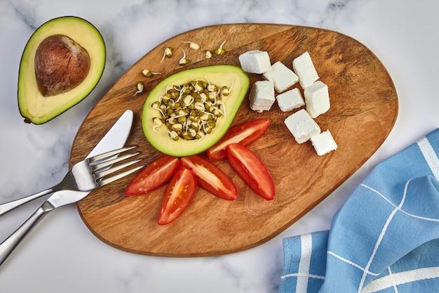 Avocado sprießt mungbohnen tomaten quark käse besteck und ein küchentuch auf einem holzbrett