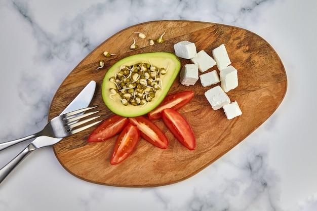 Avocado sprießt mungbohnen-tomaten-quark und besteck auf einem holzbrett auf einem leuchttisch