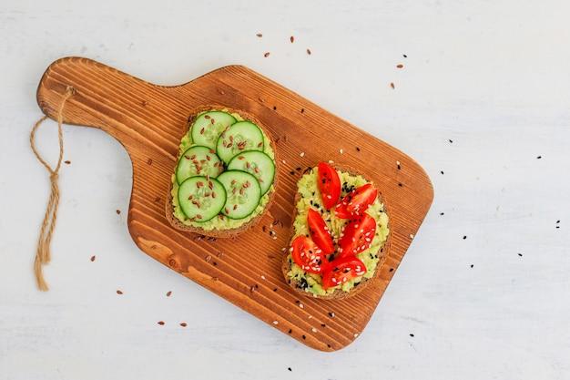 Avocado toast auf vollkornbrot mit gemüse, gelben und roten tomaten
